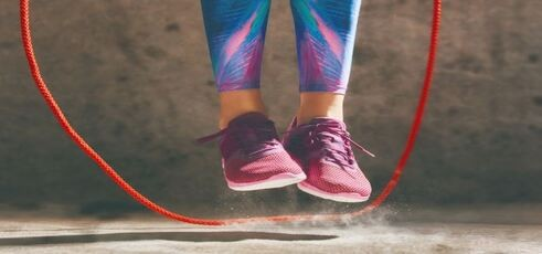 Photo of a girl's shoes skipping over a rope